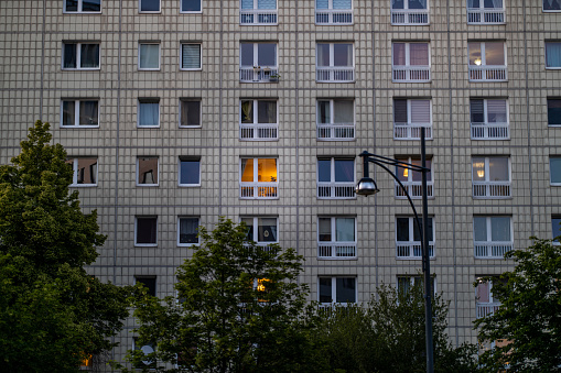 Typical socialistic building with trees and a streetlamp. Plattenbau building facade in Berlin Alexanderplatz.