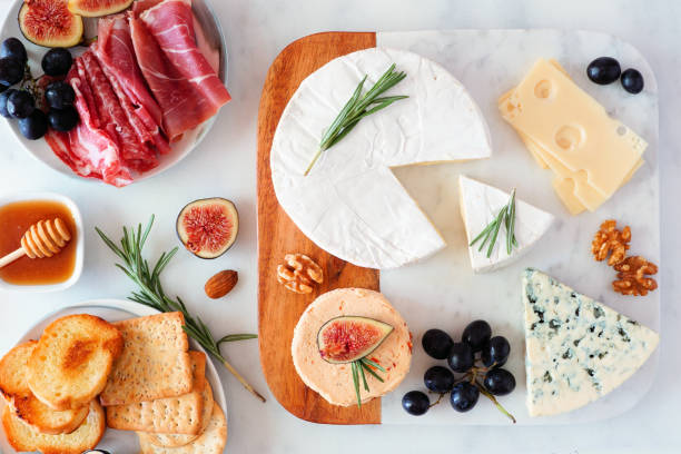 Platter of assorted cheeses and meats, top view table scene on a bright background stock photo