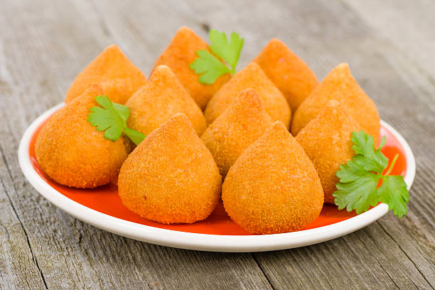 Platter of Coxinha de Galinha delights on a wooden surface Coxinha de Galinha - Brazilian deep fried chicken snack, popular at local parties. Served with chili sauce. coxinha stock pictures, royalty-free photos & images