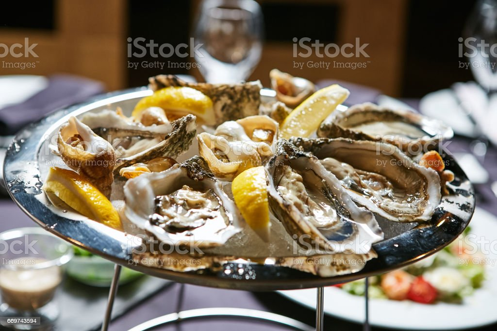 platter of fresh organic raw oysters on ice stock photo