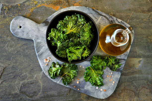 Platter of healthy kale chips, top view on slate Platter of healthy kale chips. Top view, on a dark slate background. kale stock pictures, royalty-free photos & images
