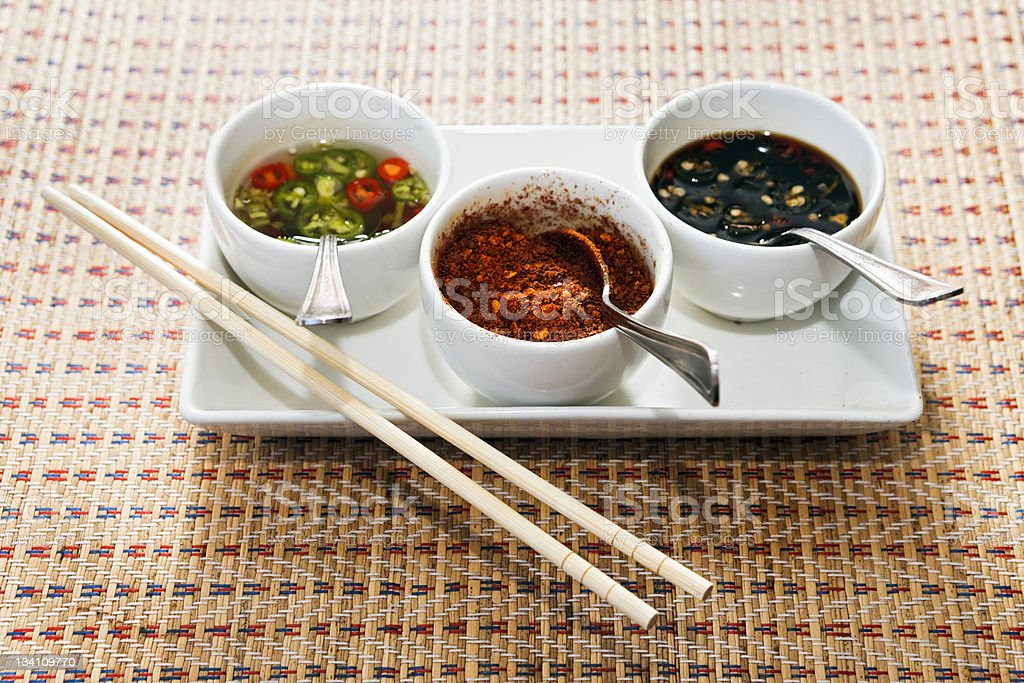 Platter of Thai condiments: chili and soy dips, ground chilis royalty-free stock photo