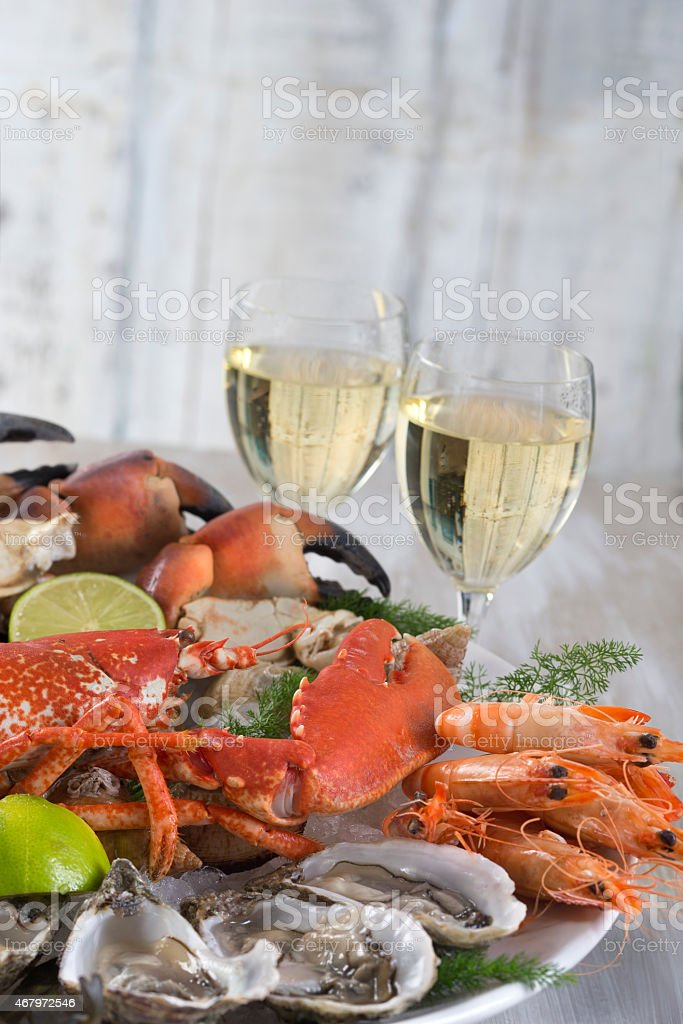 A platter of various kinds of seafood accompanied by wine stock photo