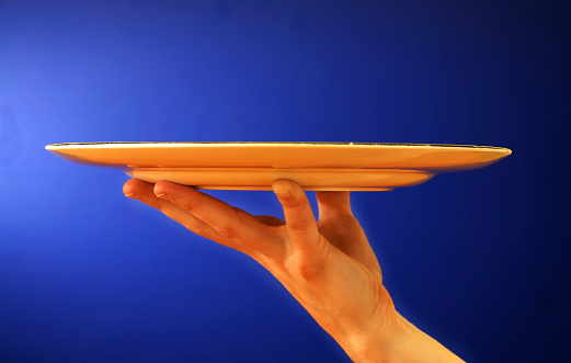 female hand holding up a platter on blue background.