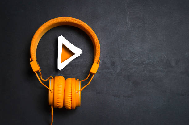 Play button Play button and orange headphones on dark concrete background mp3 player stock pictures, royalty-free photos & images