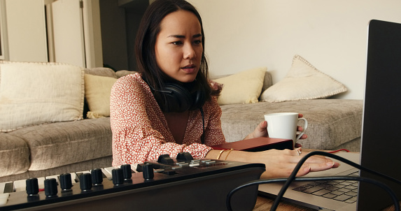 Shot of a young woman having coffee and using a laptop with her keyboard at home