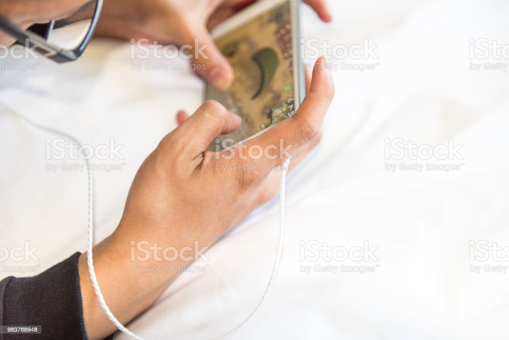 Play mobile games. Play mobile games. Bed - Furniture Stock Photo
