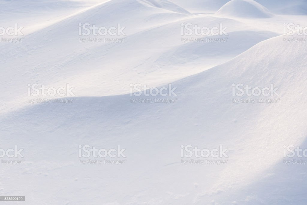 Play of light and shadow on undulating slopes of white snowdrifts. stock photo