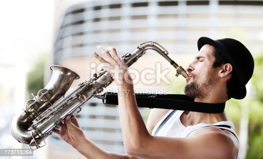 A handsome young musician playing a saxophone