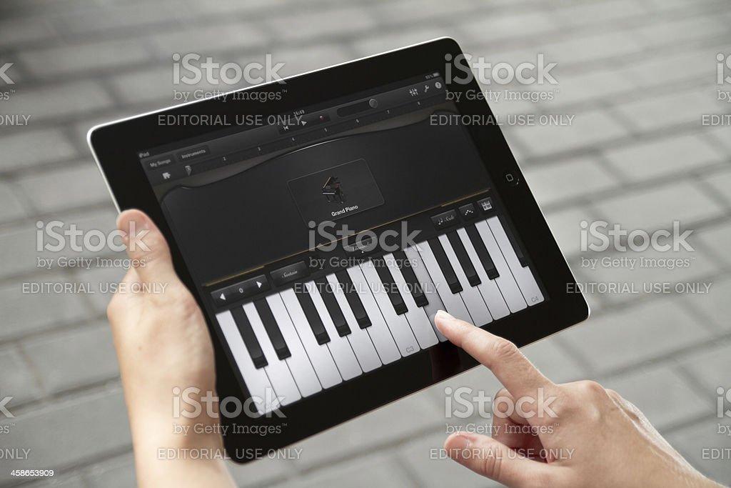 Play the piano at Apple Ipad2 royalty-free stock photo