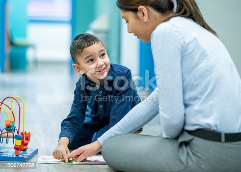 A young female, mixed race, Occupational Therapist sits cross-legged on the floor of a hospital beside her young patient.  She is dressed semi-casually in dress pants and a button-up blouse, and is engaging the young boy with an interactive bk she has laying out on the floor between them.  The young boy is kneeling on the floor in a button-up shirt as he works with the therapist.
