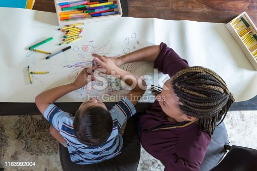 High angle view of elementary age boy with Down Syndrome coloring with female therapist during play therapy session.