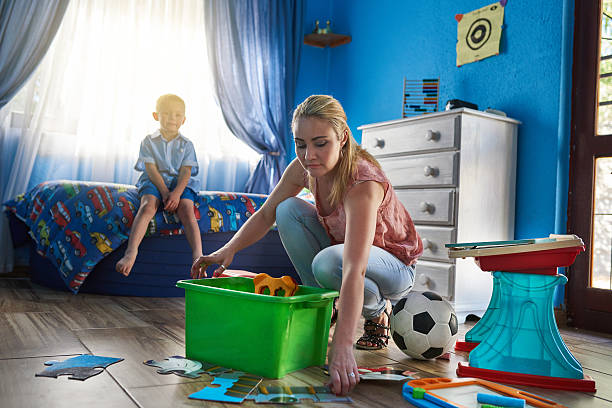Play time is over Shot of a mother packing toys away while her son sits in the background kids cleaning up toys stock pictures, royalty-free photos & images