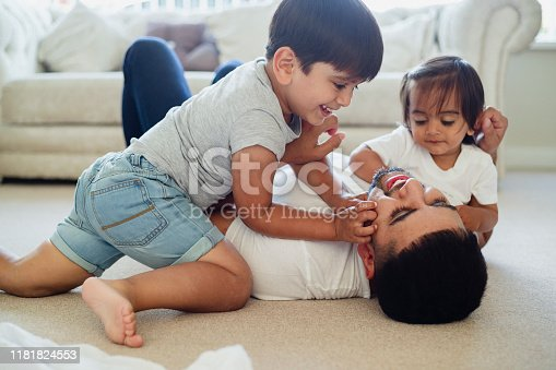A close-up shot of a father play wrestling on the floor with his two young sons, they are laughing and smiling together in the living room.