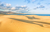 View over the landmark Maspalomas Dunes on Playa de Ingles coastline and peninsula.