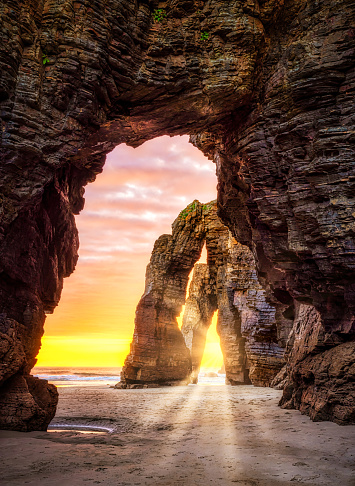 Natural rock arches in an Idyllic sunrise landscape in Cathedrals beach (playa de las catedrales), Ribadeo, Galicia, Spain
