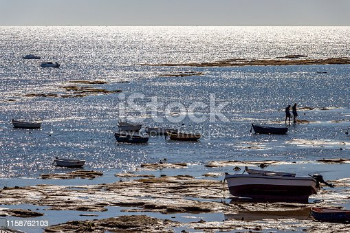 Playa la Caleta or La Caleta Beach shimmering water surface with boats in Cadiz, Province of Cadiz, Andalusia, Spain