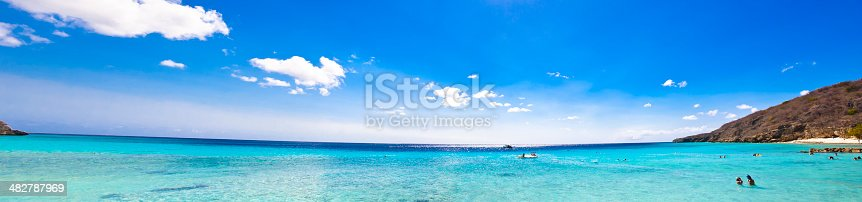 Panorama of Playa Porto Mari. Playa Porto Mari is a beautiful sandy bay on the west coast of Curacao. Its white coral sand beach, with clear and calm water, is a true paradise for water lovers. Unrecognizable people have fun in the water.