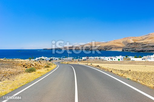 View of a panoramic road just outside the residential area of Playa Quemada, on the south-eastern coast of Lanzarote, the barren yet colourful hillocks and fields surrounding the town, a perfectly clear sky, dazzling light, deep blue waters, a beautiful day to enjoy a bicycle ride on the island. Developed from RAW.