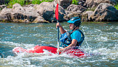 Myhiya, Ukraine - August 17, 2019: Playboating. A man sitting in a kayak with oars in his hands performs exercises on the water. Kayaking freestyle on whitewater.
