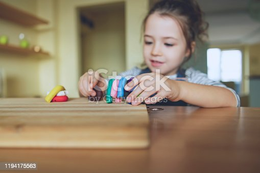 Little girl is learning to use colorful play dough
