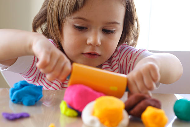 Playdough game Little girl creating toys from playdough clay stock pictures, royalty-free photos & images