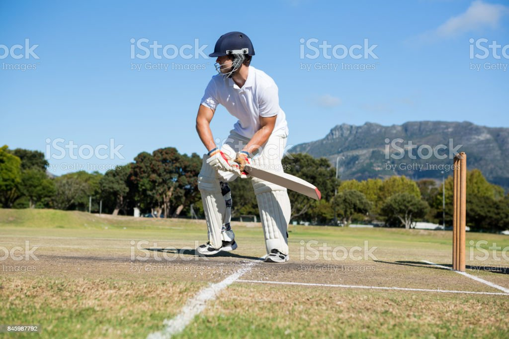 Player batting at field against clear sky stock photo