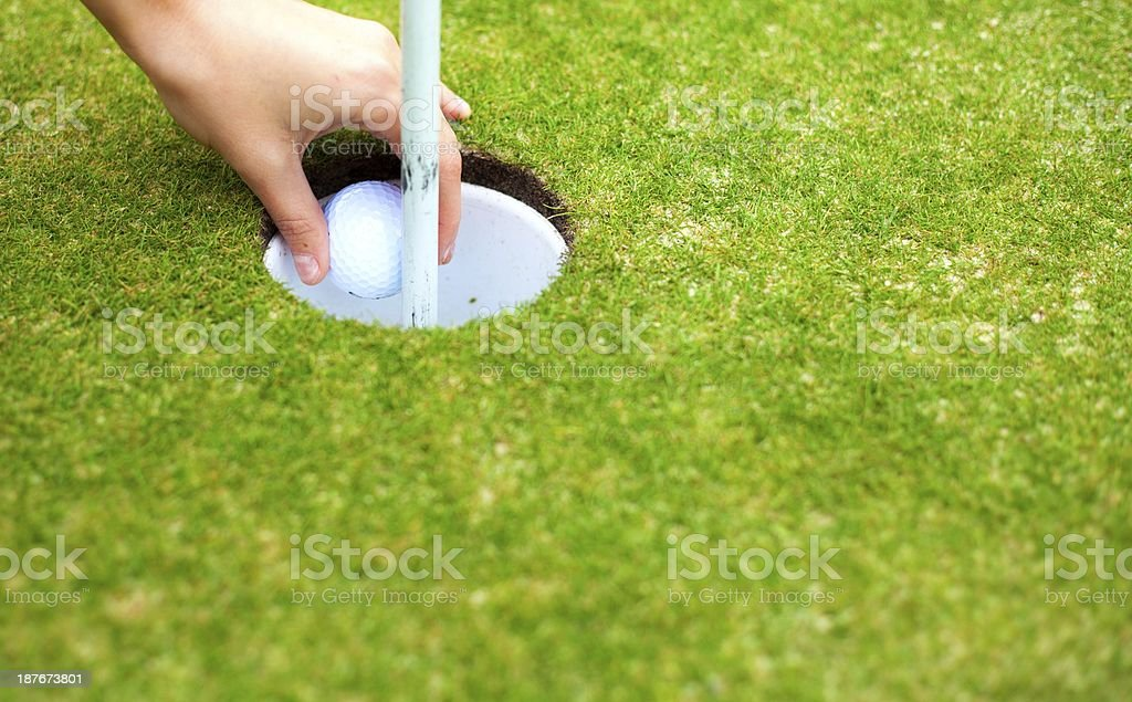 Player\'s hand removing golf ball from cup after shot