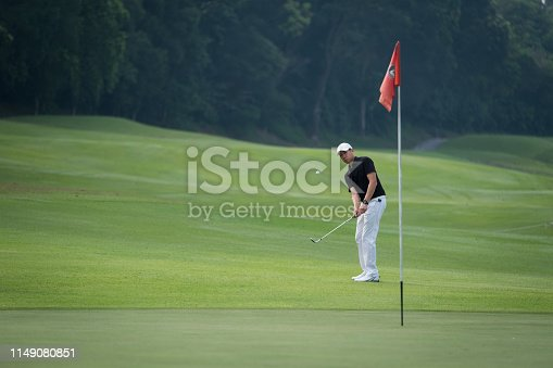Golf player taking a shot on course. Male golfer is swinging ball on green field. He is practicing during weekend summer.