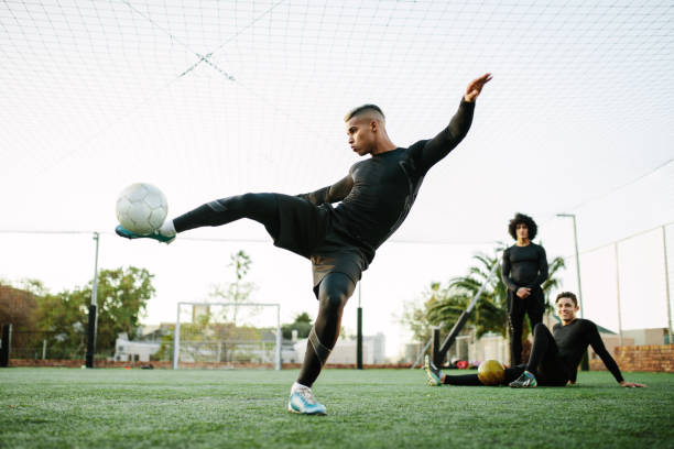 player kicking soccer ball on field - athlete stock photos and pictures