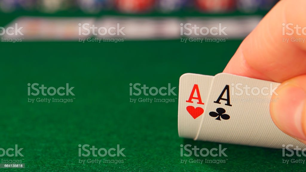 POKER: Player looks his playing cards in the game stock photo