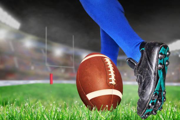Player Prepares to Kick Football Field Goal in Outdoor Stadium stock photo