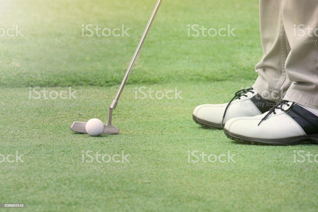 Golf player put a golf ball on a green