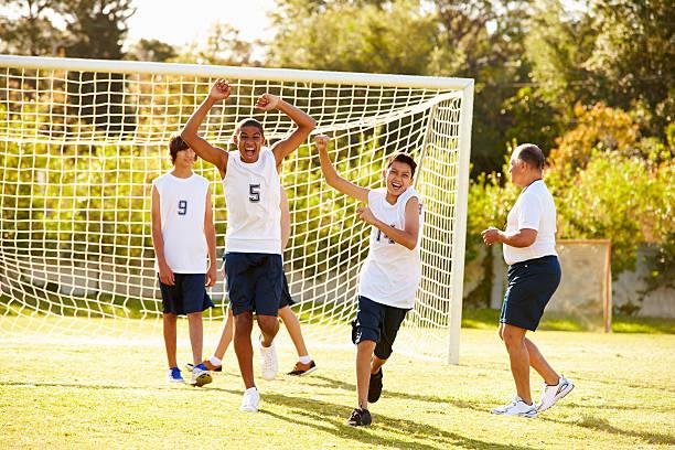 Player Scoring Goal In High School Soccer Match stock photo