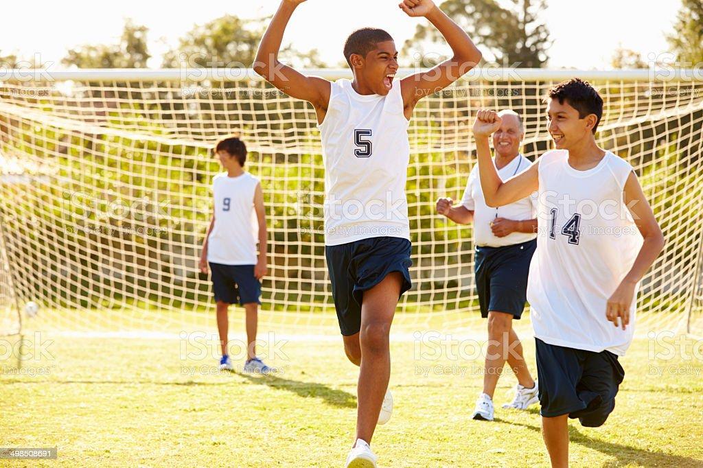 Player segnare Goal In High School partita di calcio - Foto stock royalty-free di 14-15 anni