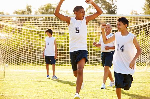 Player Segnare Goal In High School Partita Di Calcio - Fotografie stock e altre immagini di 14-15 anni