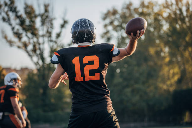NFL player throwing a ball Two men, American football players on rough training outdoors. quarterback stock pictures, royalty-free photos & images
