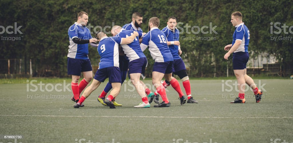 Group of people, young and strong rugby team on the field, playing...