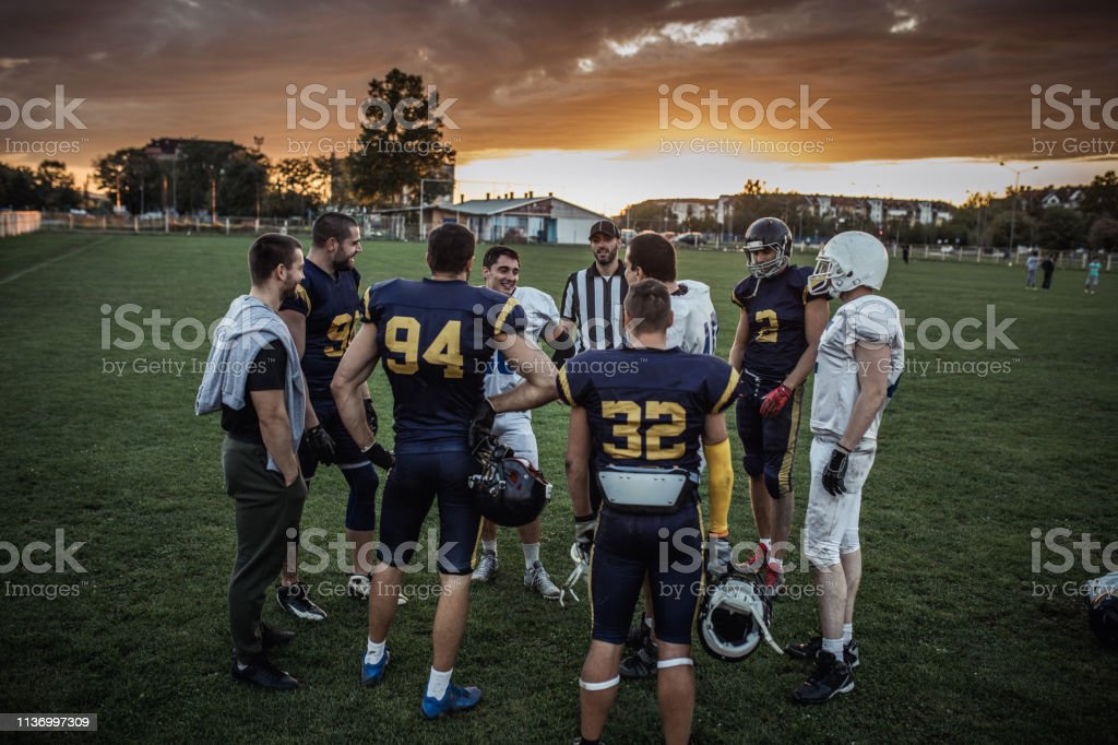 Large group of American football players standing on playing field at...
