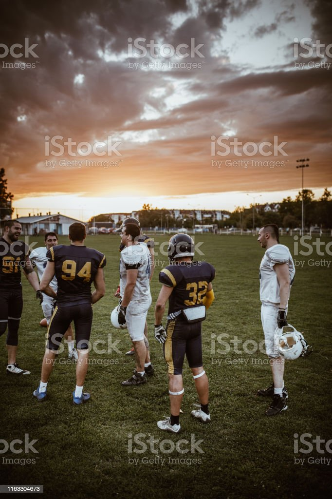 Full length of large group of American football players standing on...