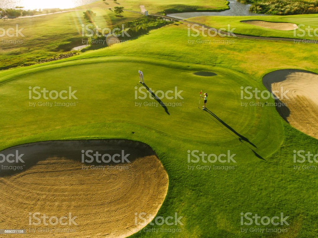 Players on a green golf course stock photo