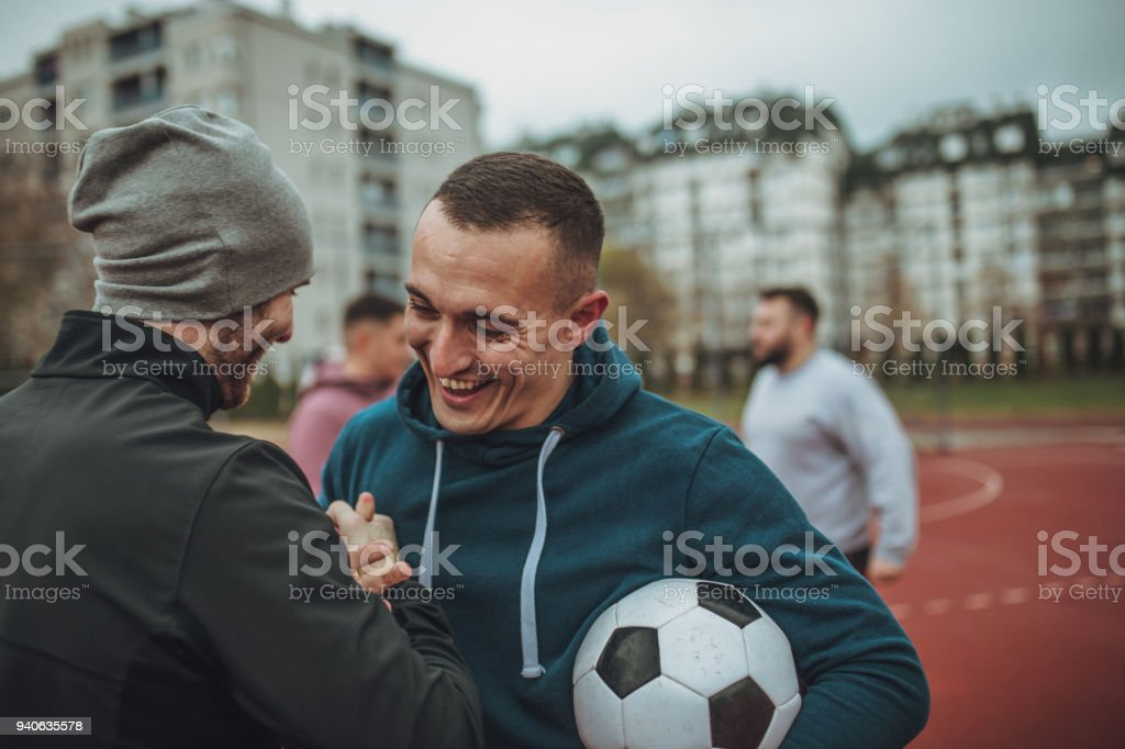 Players standing on a soccer playing field and handshake stock photo