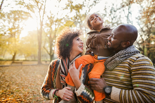 Happy African American parents holding their daughter on shoulders and having fun in autumn park.