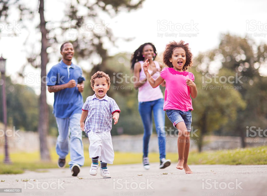 Playful African American family running in the park. royalty-free stock photo