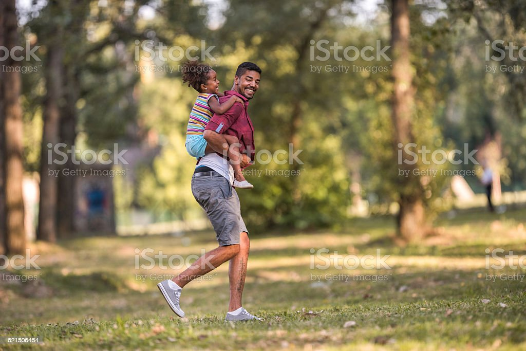 Playful African American father piggybacking his daughter in the park. Lizenzfreies stock-foto