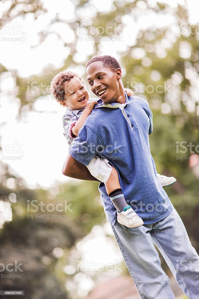 Playful African American father piggybacking his son outdoors. royalty-free stock photo