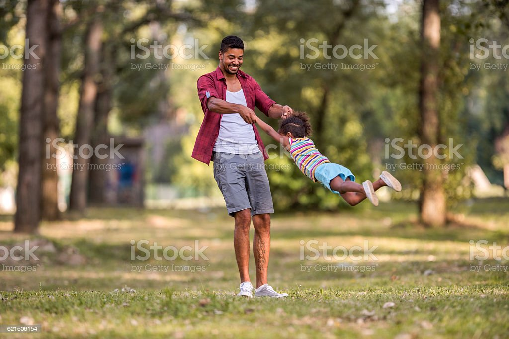 Playful African American father spinning his daughter in the park. foto stock royalty-free