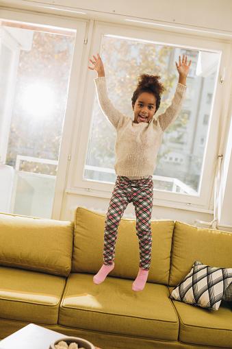 Speelse African American Girl Springen Op De Bank Thuis Stockfoto en meer beelden van Afrikaanse etniciteit