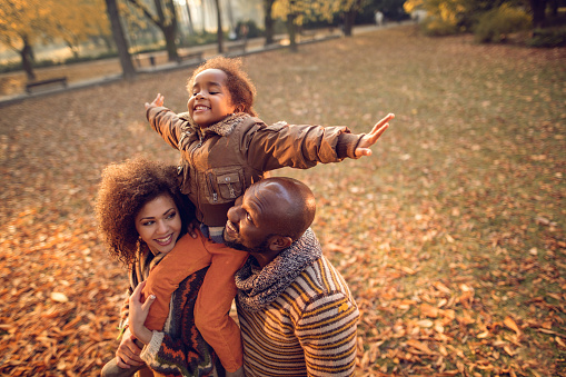 Happy African American family having fun in autumn park. Parents are holding their playful daughter on shoulders.