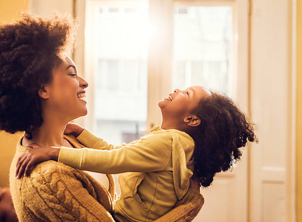 Playful African American mother and daughter having fun at home. stock photo